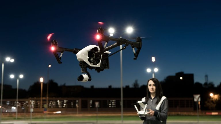 Woman flying drone at night - uas night operation