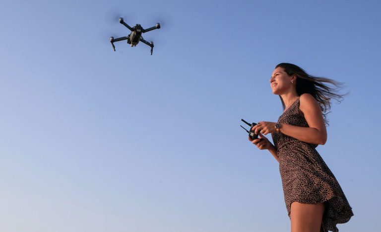 Woman flying drone - uk drone licences and regulations guide