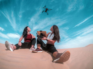 Drones and education - girls using drone in sand.